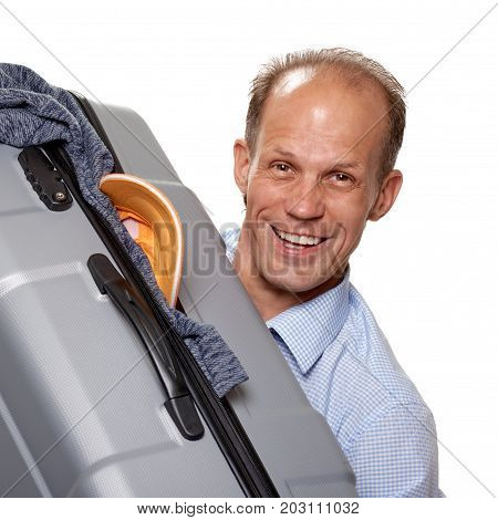 Young cheerful tourist holding big gray valise