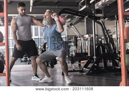 Do it slowly. Old man with beard is squatting with kettlebell in modern gym. Professional trainer is watching him with concentration. Copy space in the right side