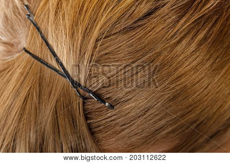 Detailed close up of brown dark blonde hair in ponytail with clips. Hairdo surface.