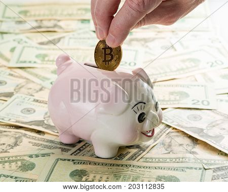 Fingers placing a single gold bitcoin coin into the slot on a piggy bank with 20 dollar notes on table