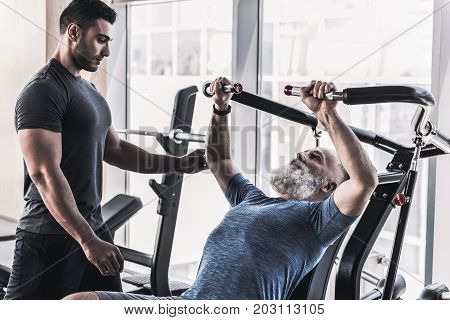 Senior bearded man is sitting at power training apparatus and hardly doing exercise in modern gym against big window. His instructor is standing nearby and watching him