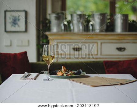 A beautiful, elegant composition of restaurant dinner on a blurred interior background. Perfectly served plate of traditional seafood and shellfood with a glass of white champagne. Copy space.