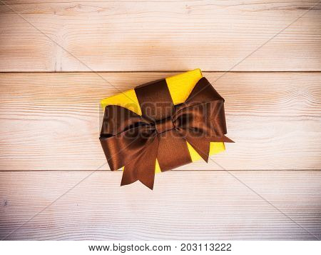 Yellow gift box on wooden board. Copy space. Holidays concept