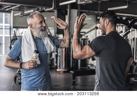 Give me five. Joyful men are standing in sport club and enjoying friendly conversation. Senior pensioner is holding bottle of water in his hand