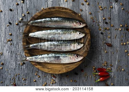high-angle shot of some raw sardines in a wooden plate, placed on a gray rustic wooden table sprinkled with peppercorns