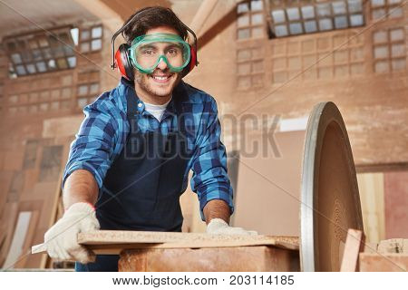 Man as artisan with protective googles and ear protection