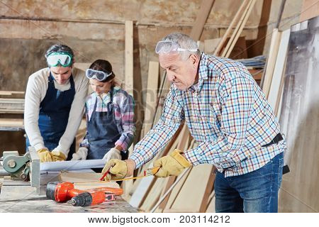Senior joiner working at carpentry workshop
