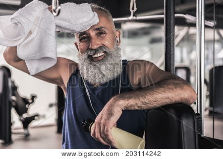 Cheerful and tired. Portrait of senior bearded man is smiling and wiping his brow with towel while looking at camera with joy. He is standing in sport center and listening to music through earphones