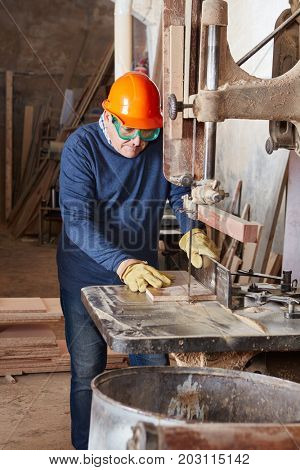 Senior citizen using band saw at workshop