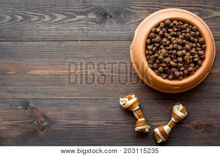 pet care with dry food for pet - dog in plastic bowl on wooden desk background top view space for text