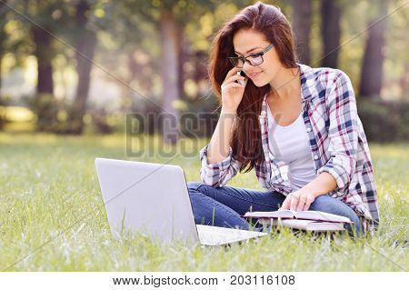 Student Girl Working On Laptop, Sitting On Grass In Park