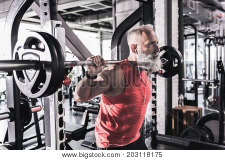 Heavy barbell. Stylish old powerful man with gray beard is lifting weight in modern sport center while listening to music through earphones
