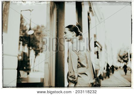 Vintage Black And White Photo Of Woman On Street Looking Into Storefront