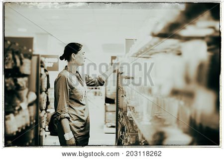 Vintage Black And White Photo Of Woman In Store Looking At Glassware