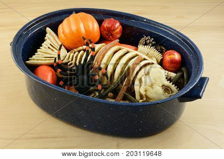 Halloween witch's brew of worms, dead fish skeleton, spider, pine cones and pumpkins in large pan