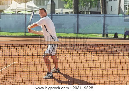 Confident sportsman is standing near net on tennis court and holding racket. He looking at camera with readiness to fight off pitch. Full length portrait. Copy space on right side