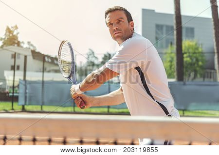 Serious sportsman is ready to beat off pitch. He standing at tennis court near grid and looking ahead with expectation. Waist up portrait