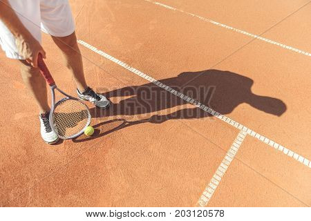 Top view of sportsman is standing at court and holding racket in vertical position. Close up of male legs. Focus on shadow. Copy space on right side