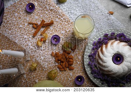 A table with a bunch of cinnamon, burning candles, almond, physalis, a glass of lemonade, a metal fork, a ring cake sprinkled with sugar powder on a light colorful background.