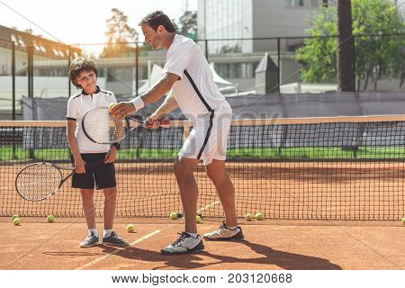 Teenage boy is holding racket and looking at racquet, his father using with curious smile. Copy space on right side