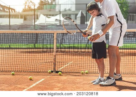 Cheerful son is learning how to hold tennis racket in right way. Father standing behind him. Copy space on left side