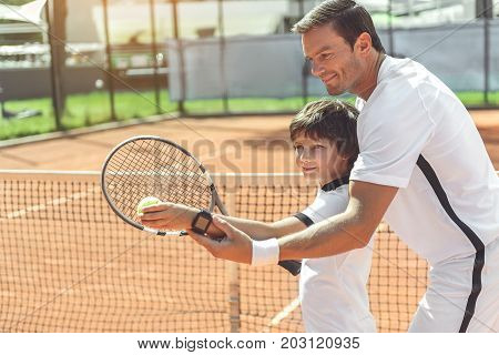 Cheerful father is standing behind son and showing how to make pitch in right way. Wait up portrait of child. Copy space on left side