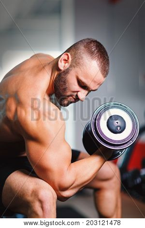 An appealing man with an athletic body lifting a dumbbell in a gym on a light blurred background. Gym, sport, weight lifting, bodybuilding concept.
