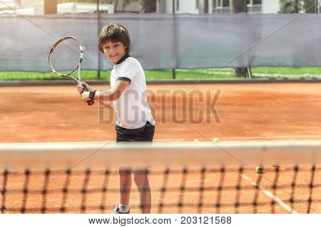 Cheerful little tennis player is holding racket and ready to beat off any pitch. He looking at camera with curiosity. Full length portrait. copy space on right side
