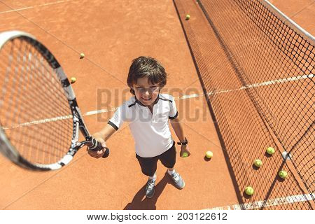 Cheerful little sportsman is standing near net and rising tennis racket up. He looking at camera with smile. Full length portrait. Top view