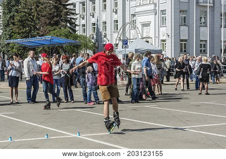 Belarus Minsk - 27.05.2017: A young man in a red T-shirt and shorts is riding roller skates