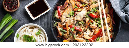 Chicken Stir fry, udon noodles and soy sause on black stone table. Traditional asian food. Long banner format.