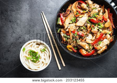 Chicken Stir fry and udon noodles on black slate table. Traditional asian food. Top view copy space.