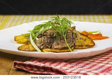 On a plate is roasted meat with potatoes carrots and greens