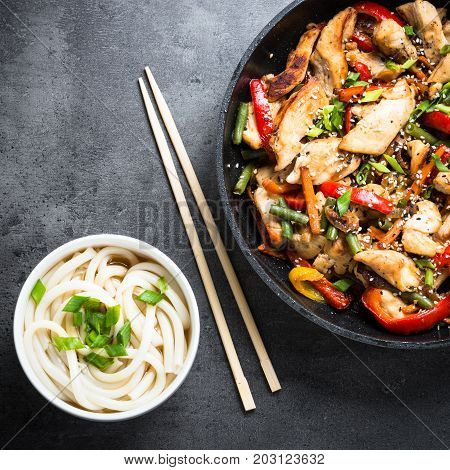 Chicken Stir fry and udon noodles on black slate table. Traditional asian food. Top view.