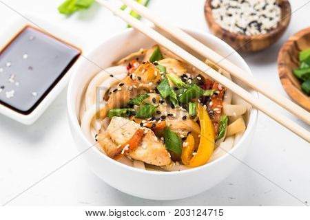 Udon stir-fry noodles with chicken  vegetables soy sause and sesame in white bowl. Traditional asian food.
