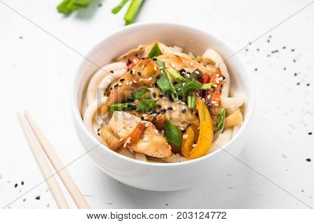 Udon stir-fry noodles with chicken  vegetables and sesame on white table. Traditional asian food.
