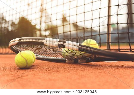 Racket and small yellow balls are locating nearby grid at court. Focus on racquet. Copy space. Close up