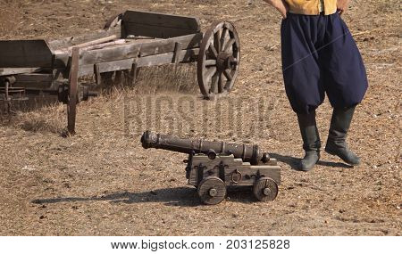 A cossack standing near small cannon on wheels and wooden cart photo.