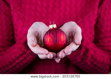 Beautiful Christmas Ball In Female Hands On Background Of Red Knitted Sweater