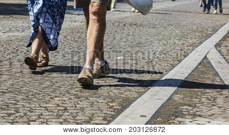 Paris- July 62017: Deatail image of the legs of an unidentified couple walking on the famous Boulevard Champs Elysees closed for car traffic. Each first Sunday of the month The Boulevard is closed for car traffic.