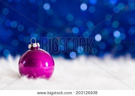 Crimson Christmas Ball On White Fur With Garland Lights On Blue Bokeh Background