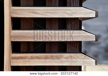 Wooden wall with panels and three horizontal panes in a lighter wood than the background wood with space for text. Blurred background.