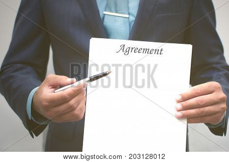 Agreement conclusion. Signing of the agreement. Business man holding blank document page in front of him and pointing pointing at him with a pen. Credit registration. Dealing.