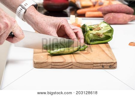 green bell pepper being chopped on a wooden chopping board