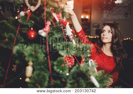 Girl is smiling decorating Christmas tree x-mas.
