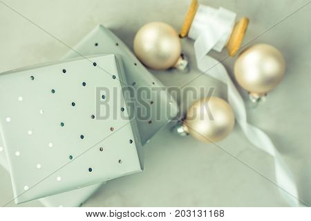 Stacked gift boxes wrapped in grey silver paper with polka dots pattern. Wooden spool with white silk ribbon Christmas balls on stone marble background. Top view copy space.
