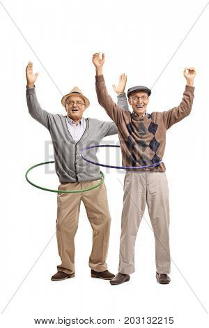 Full length portrait of two cheerful elderly men with hula hoops isolated on white background