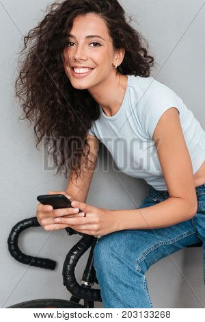 Vertical close up image of smiling curly sitting on bicycle, using smartphone and looking at the camera over gra background