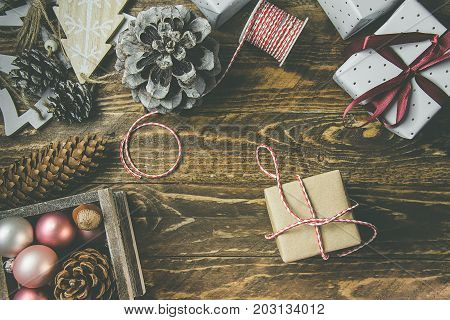 Flat lay on rustic aged wood background Christmas or New Years gits wrapped in craft brown and white paper. Ribbon twine pine cones baubles ornaments. Kinfolk hygge style.