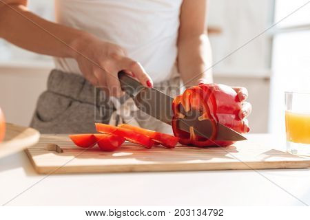 Close up portrait of young woman slicing capsicum on a cutting board indoors